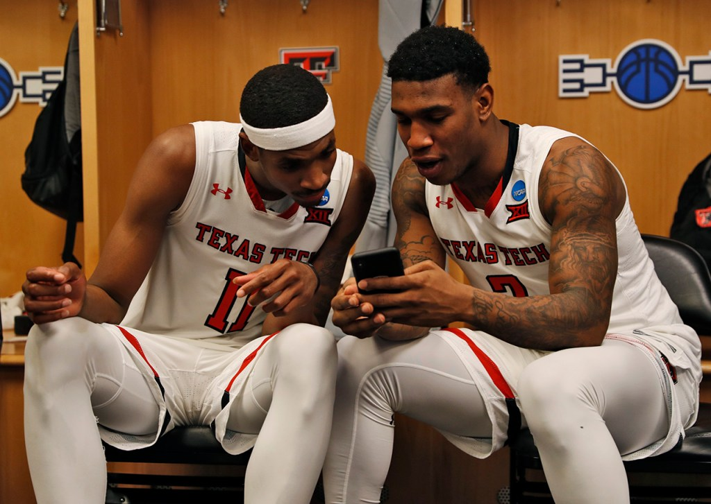 Texas Tech's Tariq Owens looks at Deshawn Corprew's phone in the locker room after the NCAA tournament second round game against Buffalo, Sunday, March 24, 2019, at BOK Center in Tulsa, Okla. [Brad Tollefson/A-J Media]