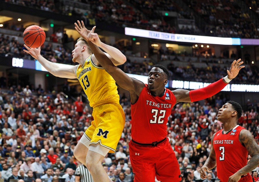 Michigan's Ignas Brazdeikis (13) rebounds the ball away from Texas Tech's Norense Odiase (32) during the NCAA tournament Sweet 16 game Thursday, March 28, 2019, at Honda Center in Anaheim, Calif. [Brad Tollefson/A-J Media]