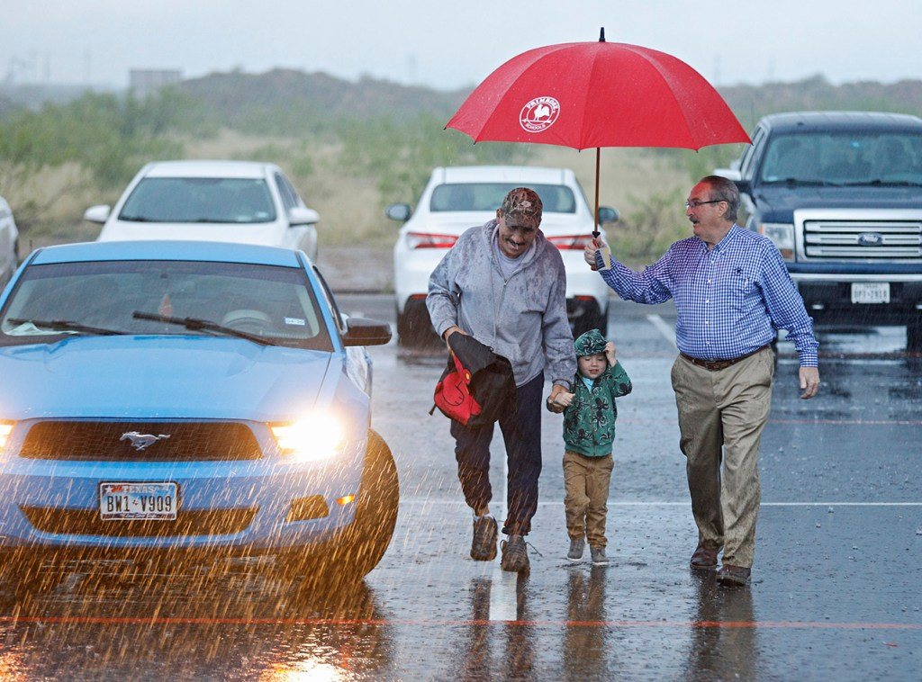 Michael McLaguhlin, franchise owner, holds an umbrella for Servando Carrasco and Noah Carrasco while walking into Primrose School of Midland at Westridge on Tuesday, April 23, 2019 in Midland, Texas. (Brad Tollefson/AP Images for Primrose Schools)