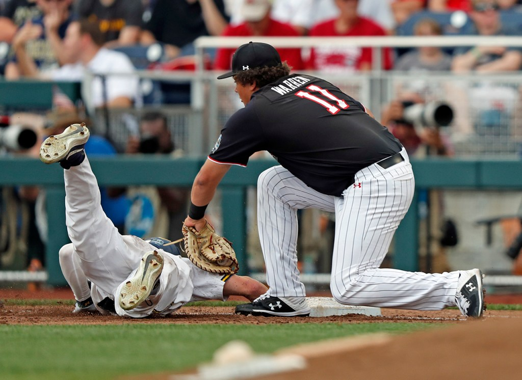 Michigan's Jesse Franklin (7) slides back into first base around Texas Tech's Cameron Warren (11) during the College World Series game against Michigan, Saturday, June 15, 2019, at TD Ameritrade Park in Omaha, Neb. [Brad Tollefson/A-J Media]