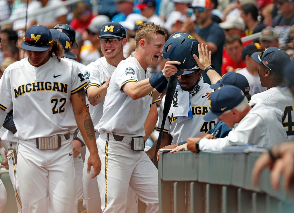 Michigan's Jimmy Kerr (15) celebrates with his teammates after scoring a run during the College World Series game against Texas Tech, Friday, June 21, 2019, at TD Ameritrade Park in Omaha, Neb. [Brad Tollefson/A-J Media]