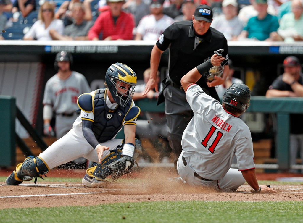 Texas Tech's Cameron Warren (11) slides into home plater around Michigan's Joe Donovan (0) during the College World Series game against Michigan, Friday, June 21, 2019, at TD Ameritrade Park in Omaha, Neb. [Brad Tollefson/A-J Media]