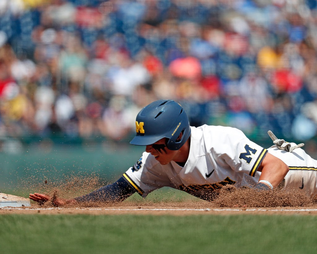 Michigan's Blake Nelson (10) dives back into first base during the College World Series game against Texas Tech, Friday, June 21, 2019, at TD Ameritrade Park in Omaha, Neb. [Brad Tollefson/A-J Media]