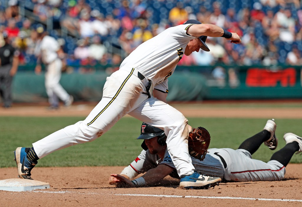 Texas Tech's Easton Murrell (19) its tagged out diving back into first base by Michigan's Jimmy Kerr (15) during the College World Series game Friday, June 21, 2019, at TD Ameritrade Park in Omaha, Neb. [Brad Tollefson/A-J Media]