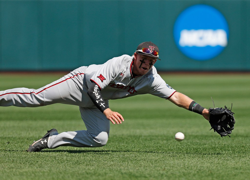 Texas Tech's Brian Klein (5) dives to catch a fly ball during the College World Series game against Michigan, Friday, June 21, 2019, at TD Ameritrade Park in Omaha, Neb. [Brad Tollefson/A-J Media]