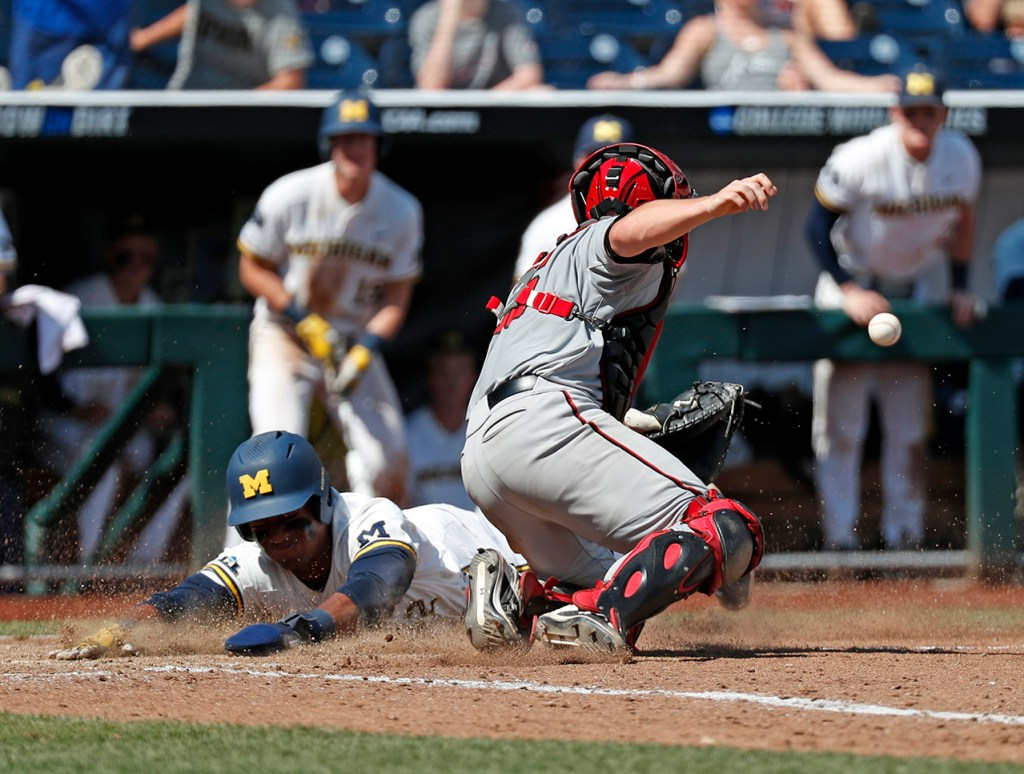 Michigan's Ako Thomas (4) scores a run around Texas Tech's Braxton Fulford (26) during the College World Series game against Michigan, Friday, June 21, 2019, at TD Ameritrade Park in Omaha, Neb. [Brad Tollefson/A-J Media]