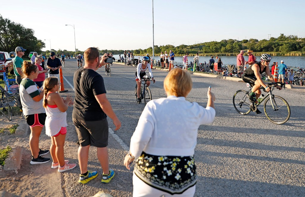Fans cheer for bike riders during the Ironman 70.3 Lubbock, Sunday, June 30, 2019, at Dunbar Lake in Lubbock, Texas. [Brad Tollefson/A-J Media]