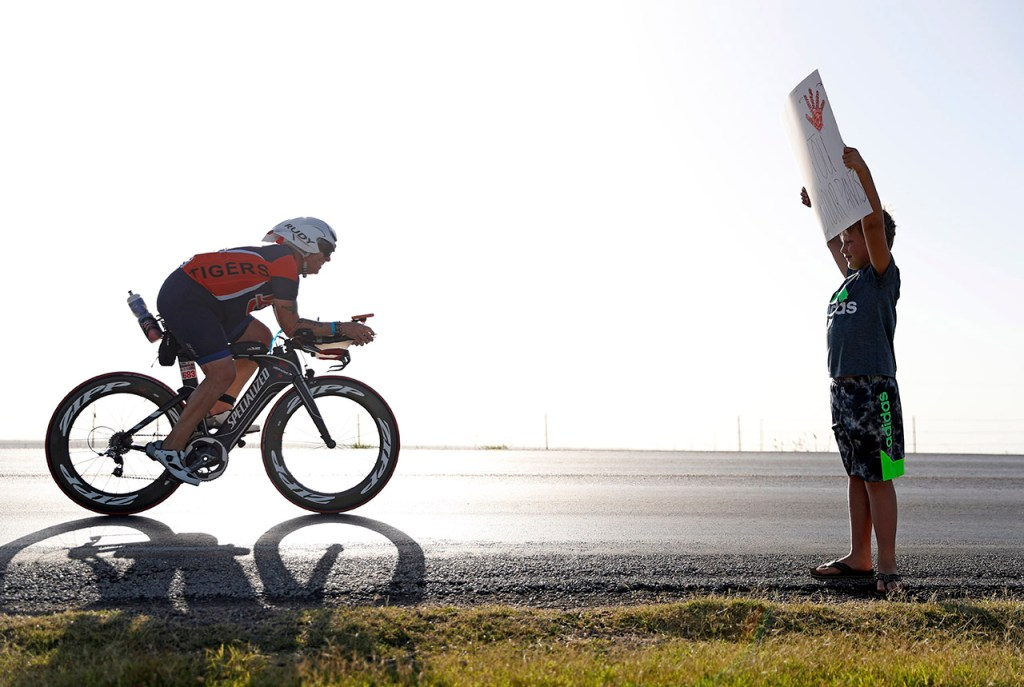 "Simon Manning, from Plainview, holds up a sign that reads ""Wave if you peed your pants"" as David Pritchett, from Richmond, rides by during the Ironman 70.3 Lubbock, Sunday, June 30, 2019, near Slaton, Texas. [Brad Tollefson/A-J Media]"
