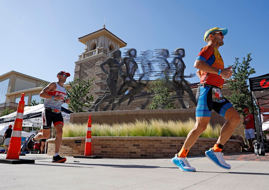 "Jesse Danner, from Grand Prairie, and Michael Minardi, from Cedar Park, run past the statue titled ""Run"" during the Ironman 70.3 Lubbock, Sunday, June 30, 2019, at Texas Tech in Lubbock, Texas. [Brad Tollefson/A-J Media]"