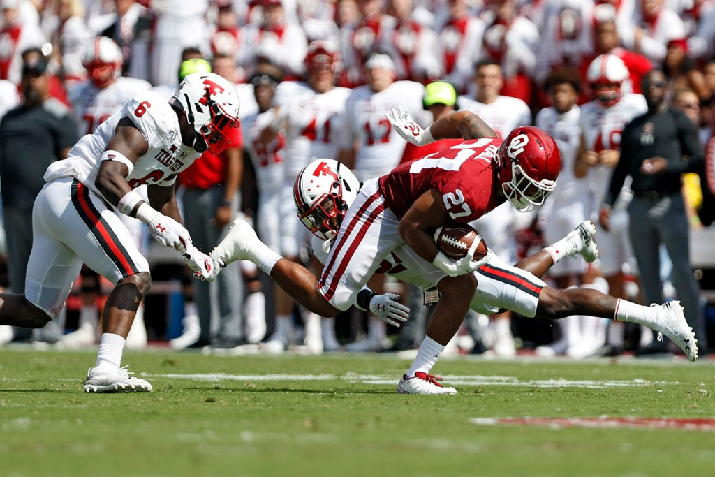 Oklahoma's Jeremiah Hall (27) breaks a tackle by Texas Tech's Adam Beck (24) and Riko Jeffers (6) during the game Saturday, Sept. 28, 2019, at Gaylord Memorial Stadium in Norman, Okla. [Brad Tollefson/A-J Media]