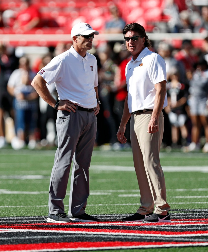 Texas Tech coach Matt Wells and Oklahoma State coach Mike Gundy talk to each other before the game Saturday, Oct. 5, 2019, in Lubbock, Texas. (AP Photo/Brad Tollefson)