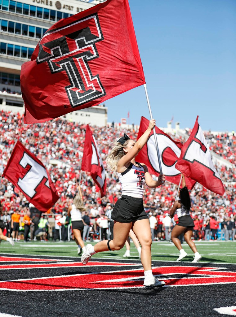 Jessica Stiglmeier, a Texas Tech cheerleader, runs with the Double T flag after a touchdown during the game against Oklahoma State, Saturday, Oct. 5, 2019, in Lubbock, Texas. (AP Photo/Brad Tollefson)