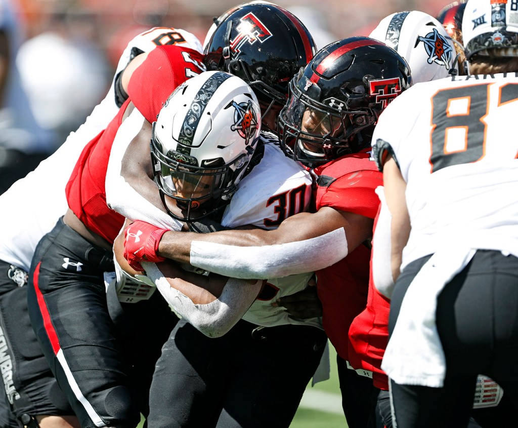 Texas Tech's Xavier Benson (37) and Jordyn Brooks (1) tackle Oklahoma State's Chuba Hubbard (30) during the game Saturday, Oct. 5, 2019, in Lubbock, Texas. (AP Photo/Brad Tollefson)