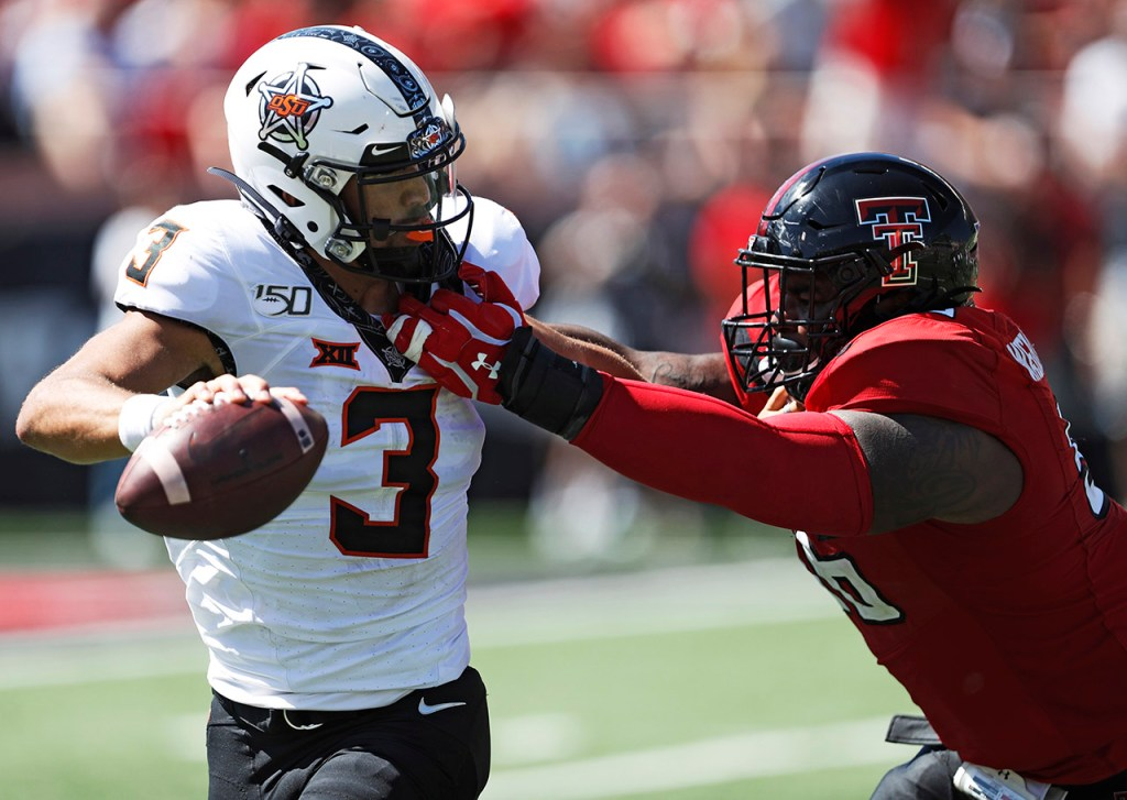 Texas Tech's Broderick Washington Jr. (96) tackles Oklahoma State's Spencer Sanders (3) during the game Saturday, Oct. 5, 2019, in Lubbock, Texas. (AP Photo/Brad Tollefson)