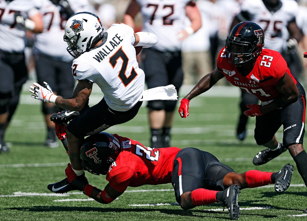 Texas Tech's Adam Beck (24) tackles Oklahoma State's Tylan Wallace (2) during the game Saturday, Oct. 5, 2019, in Lubbock, Texas. (AP Photo/Brad Tollefson)