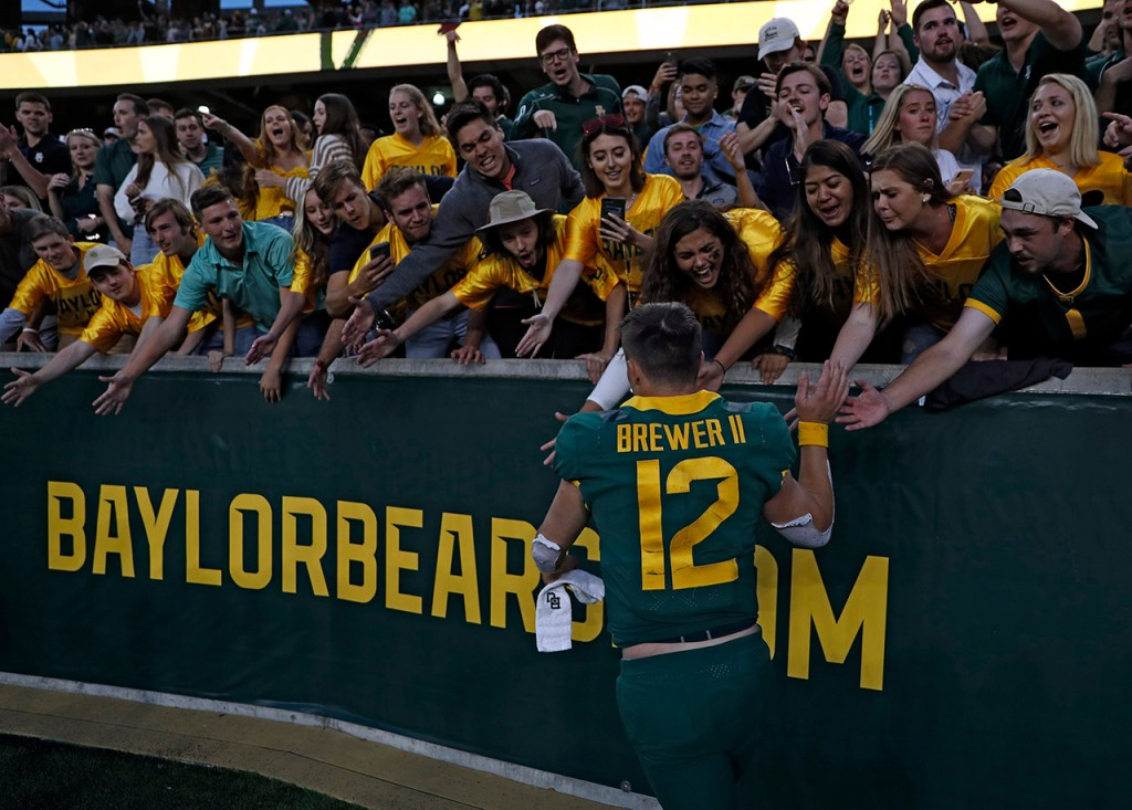 Baylor's Charlie Brewer (12) high-fives fans while running off the field after the game against Texas Tech, Saturday, Oct. 12, 2019, at McLane Stadium in Waco, Texas. [Brad Tollefson/A-J Media]