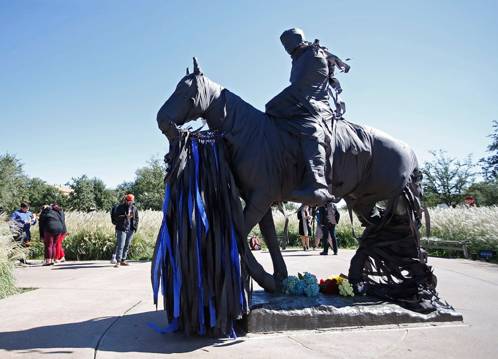 The statue of Will Rogers and Soapsuds is wrapped in black and blue crepe paper following the shooting of Floyd East Jr., Tuesday, Oct. 10, 2017, in Lubbock, Texas. [Brad Tollefson/Lubbock Avalanche-Journal]