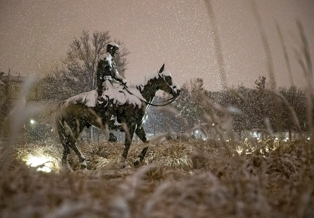 Snow falls around the statue of Will Rogers and Soapsuds during a snowstorm Saturday, Dec. 8, 2018, in Lubbock, Texas. [Brad Tollefson/Lubbock Avalanche-Journal]