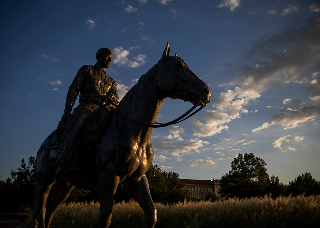 The sun sets behind the statue of Will Rogers and Soapsuds, Monday, Sept. 2, 2019, in Lubbock, Texas. [Brad Tollefson/Lubbock Avalanche-Journal]