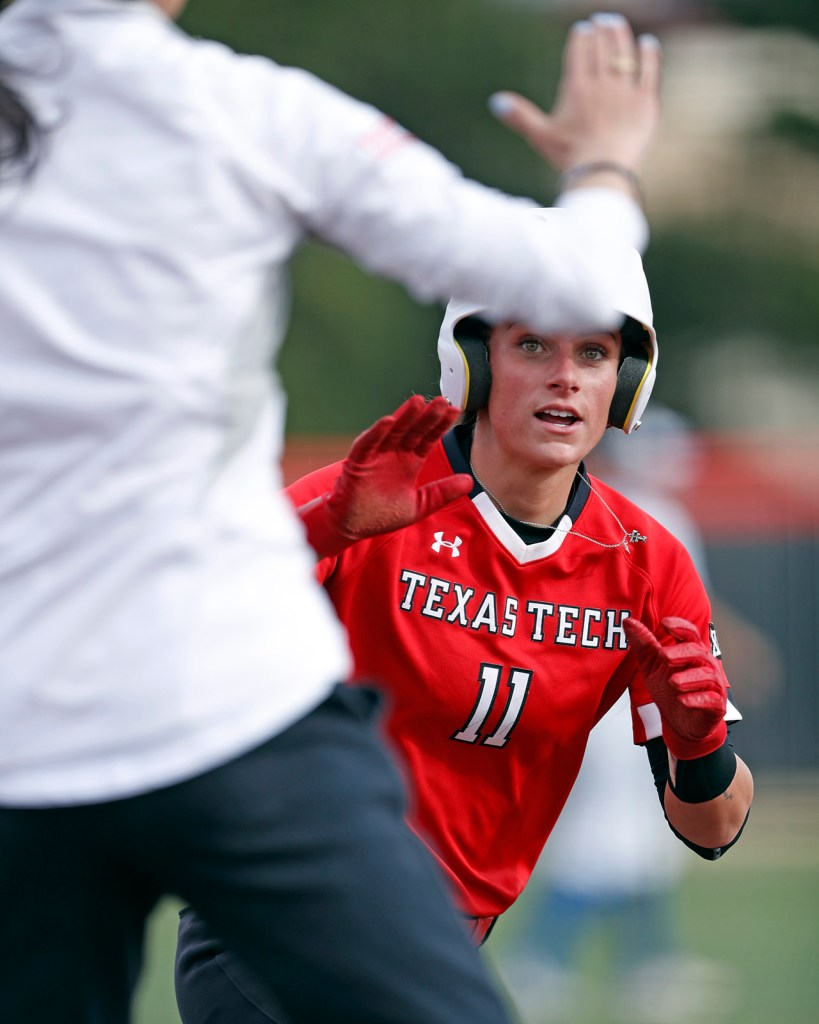 Texas Tech's Taylor Satchell (11) goes to high-five coach Adrian Gregory on her way to score a run during the game against Texas-Arlington, Friday, March 1, 2019, at Rocky Johnson Field in Lubbock, Texas. [Brad Tollefson/A-J Media]