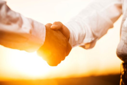 Two businessmen shaking hands at sunset.