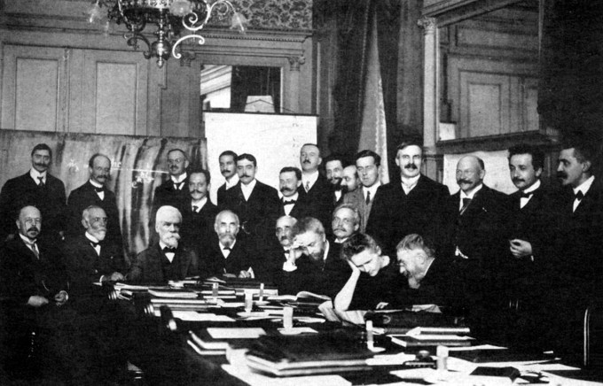 At the 1911 Solvay Conference. Curie leaning on table. Einstein second from right. Also in attendance: Max Planck, Henri Poincaré, and Ernest Rutherford.