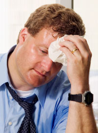 Photo: Man in suit, sweating and wiping head with cloth.
