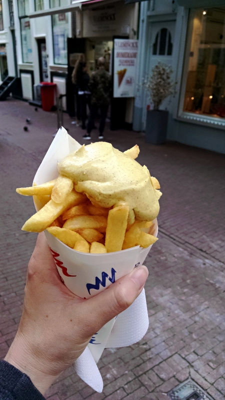 [image: french fries in a paper cone, topped with yellow curry sauce]
