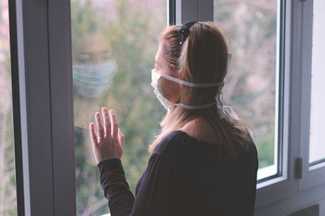 Woman in isolation, staring out side wishfully