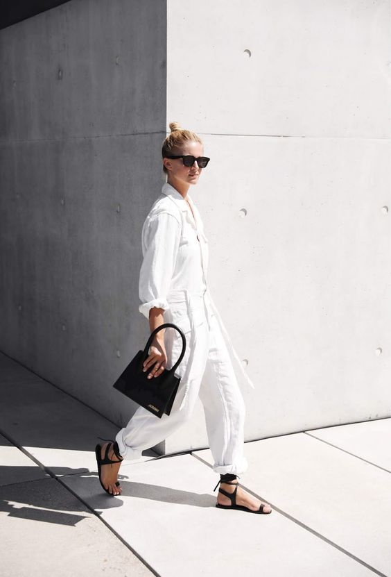 model wearing white jumpsuit and black bag