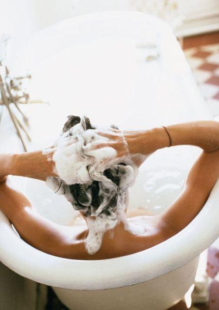 model washing hair in the bath