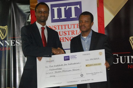 Director of Corporate Relations, Guinness Nigeria Plc, Mr. Sesan Sobowale presenting a Cheque to the Director of the Institute of Industrial Technology (IIT) Mr. Olumide Akinjo