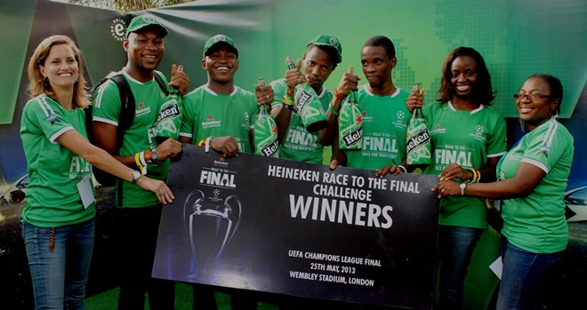 Senior Brand Manager, Heineken, Jacqueline Van Faasen first from left and Brand Manager, Heineken, Mrs. Kehinde Kadiri first from right both of Nigerian Breweries Plc presenting a dummy ticket to winners of the Heineken race to the finals Challenge second from left, Nwafor Felix Amobichukwu, George Mayowa Opeyemi, Isaac Onochie Ijeh, Franklin Chukwu Ijeh and Diana Nwajiaku-Smart all billed to travel to Wembley Stadium, London to watch the finals of UEFA Champions League with all expense paid trip courtesy of Nigeria Breweries Plc