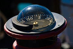 Compass on deck of derelict fishing ship, by mikebaird