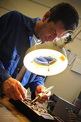 Civilian Technician Inspects Circuit Board at Army Aviation Centre Middle Wallop, by UK Ministry of Defence