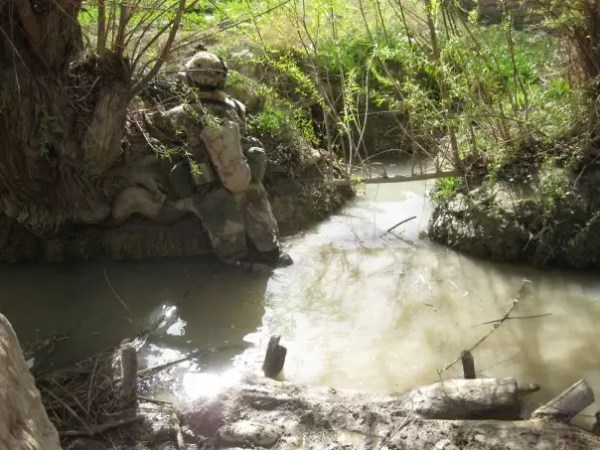 Mary dipping something into Afghan ditch water