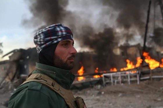 A Kurdish Peshmerga soldier passes by tires set afire days before by ISIS extremists to hinder airstrikes on November 15, 2015, in Sinjar, Iraq. # John Moore / Getty
