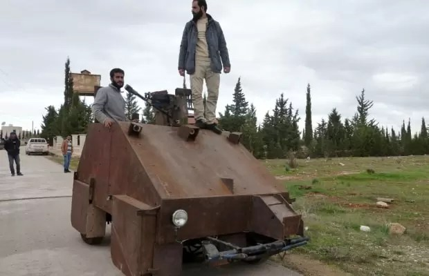 """Syrian rebels stand atop Sham II, a homemade armoured vehicle made by the rebels' Al-Ansar brigade, in Bishqatin, 4 kms west of Aleppo, on December 8, 2012. From a distance it looks rather like a big rusty metal box but closer inspection reveals the latest achievement of Syrian rebels: a homemade armoured vehicle waiting to be deployed. Sham II, named after ancient Syria, is built from the chassis of a car and touted by rebels as """"100 percent made in Syria."""" AFP PHOTO/HERVE BARHERVE BAR/AFP/Getty Images"""