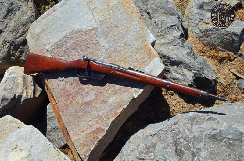 A Steyr M95 rifle displayed on a grey rock background.