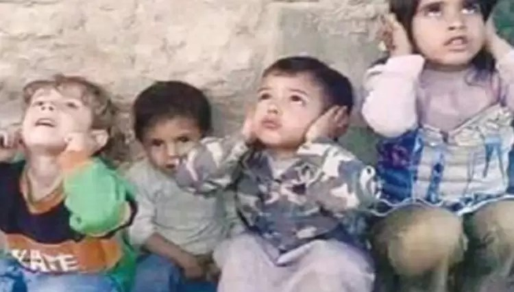 Children during the Syrian war block their ears from the sound of approaching warplanes, shelling, or cluster bombs.