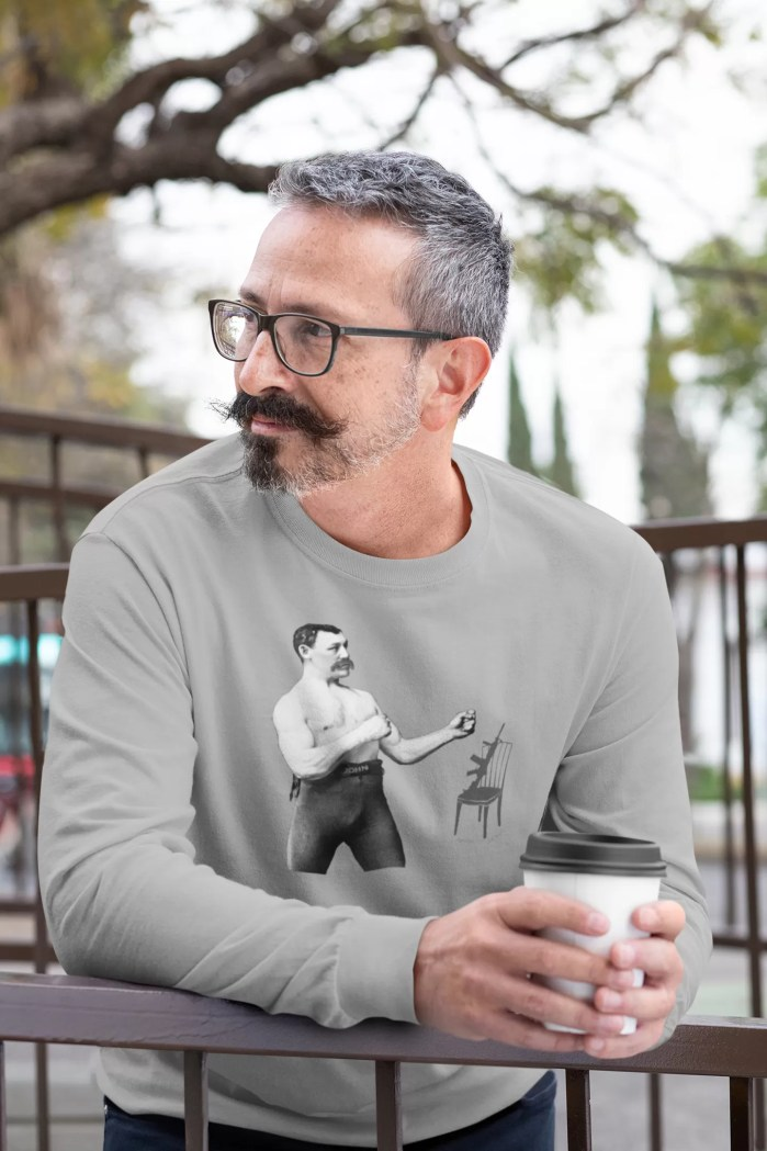 """Man wearing """"The chair is against the wall"""" shirt and drinking coffee."""