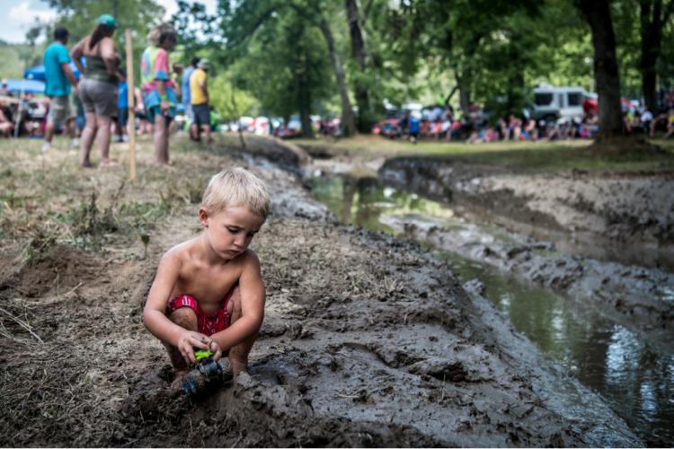 Toddler playing in the mud by Hurricane Creek at Loretta Lynn Ranch during TrailJam 2020.