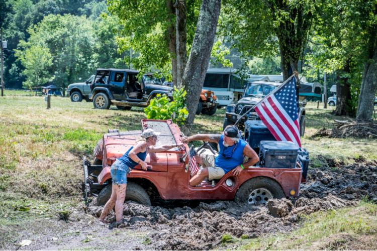 Topless Jeep with American flag stuck in a mud bog at Loretta Lynn Ranch TrailJam 2020.
