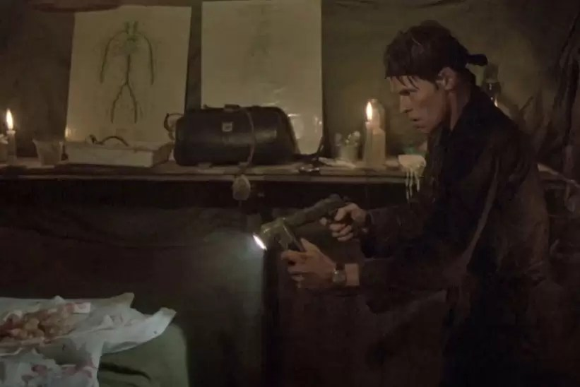 Sgt. Elias (Willem Dafoe) searching a Viet Cong tunnel complex with a right angle flashlight and a 1911 pistol in the file Platoon.