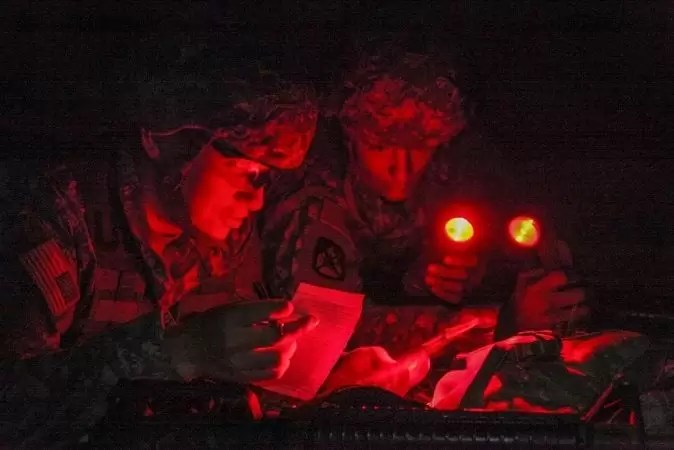 A red lens angle head flashlight in use by soldiers at night.