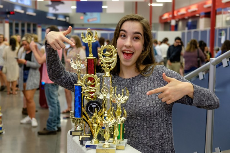Photograph of Lanie with her speech and debate trophies