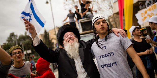 An ultra orthodox man and a young Jewish Israeli dance together at the old Mashbir Square, celebrating for the upcoming Jewish holiday of Purim, in central Jerusalem, on March 13, 2016. (Photo by Corinna Kern/Flash90)