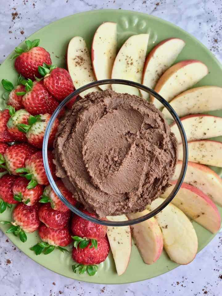 Green plate with apple slices and strawberries on it, with a small bowl of chocolate peanut butter dessert hummus in the center.