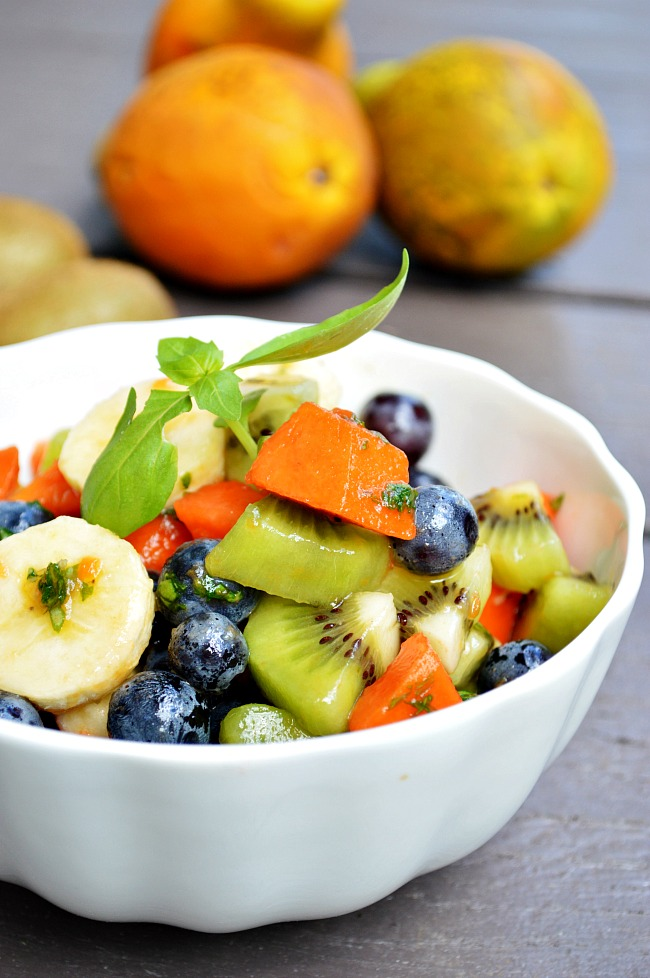 Summer or not, this Lime and Basil Tropical Fruit Salad is sure to cool you down and transport you to paradise. Strawberry papaya, banana, kiwi, and Thomcord grapes make this a special treat!