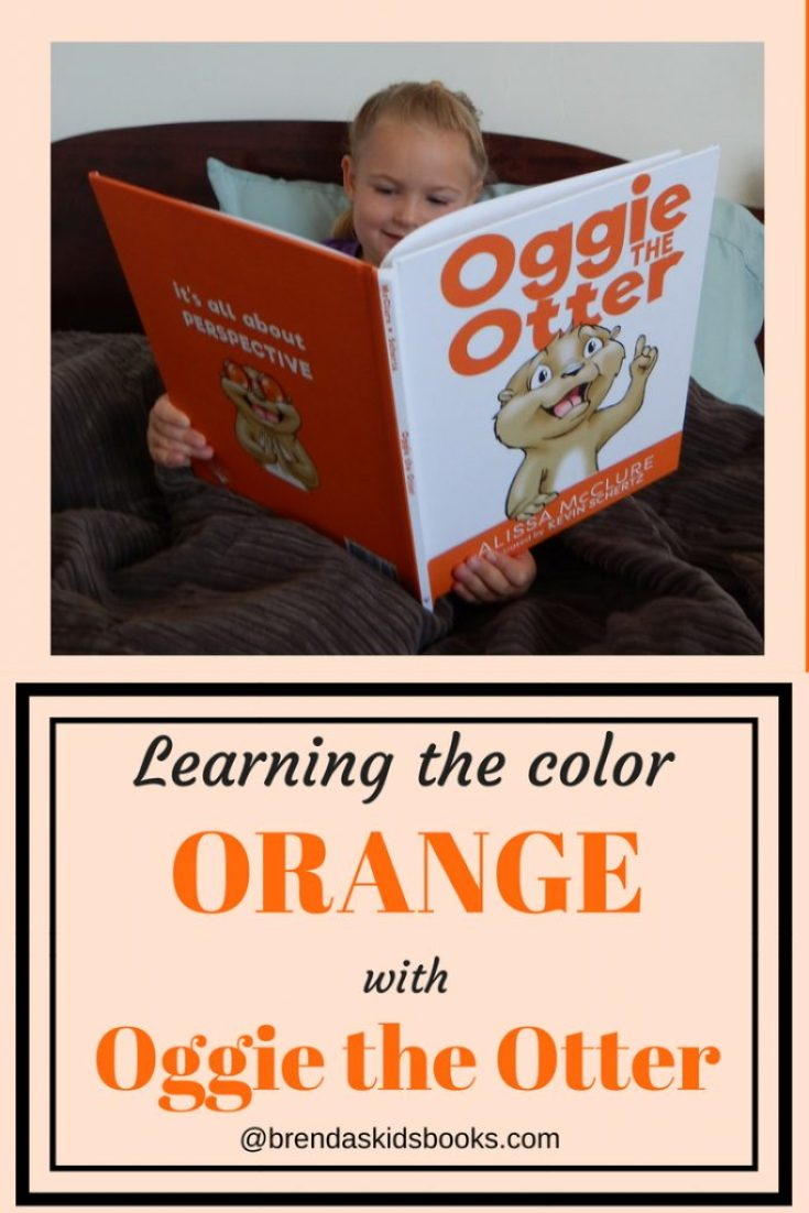 Little blonde headed girl reading a bedtime story Oggie the Otter. Learning the color orange with Oggie the Otter